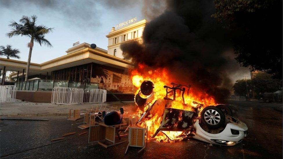 A car is seen on fire outside the O'Higgins hotel in Viña del Mar