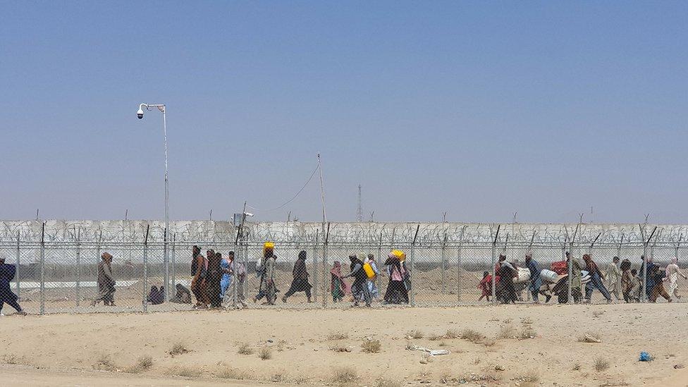 Los afganos caminan entre vallas en la frontera entre Afganistán y Pakistán