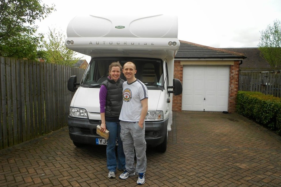 Dan and Esther stand in front of their campervan