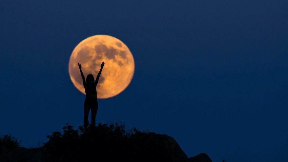 Una luna llena anaranjada, con una mujer frente a ella, con los brazos en alto.