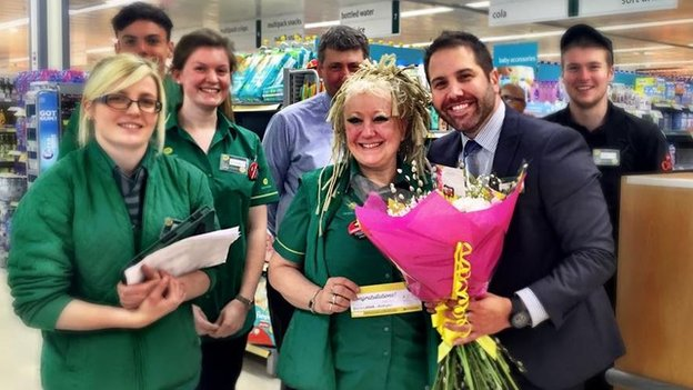 Store manager Simon Nellis presents flowers to cashier Lin