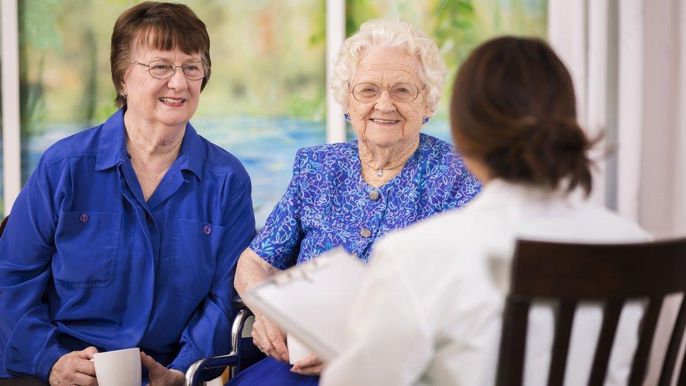 Mujeres mayores con doctora en casa para ancianos.