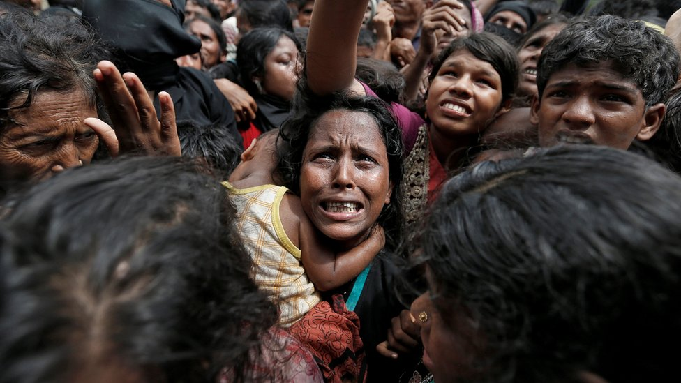 A woman reacts as Rohingya refugees wait to receive aid