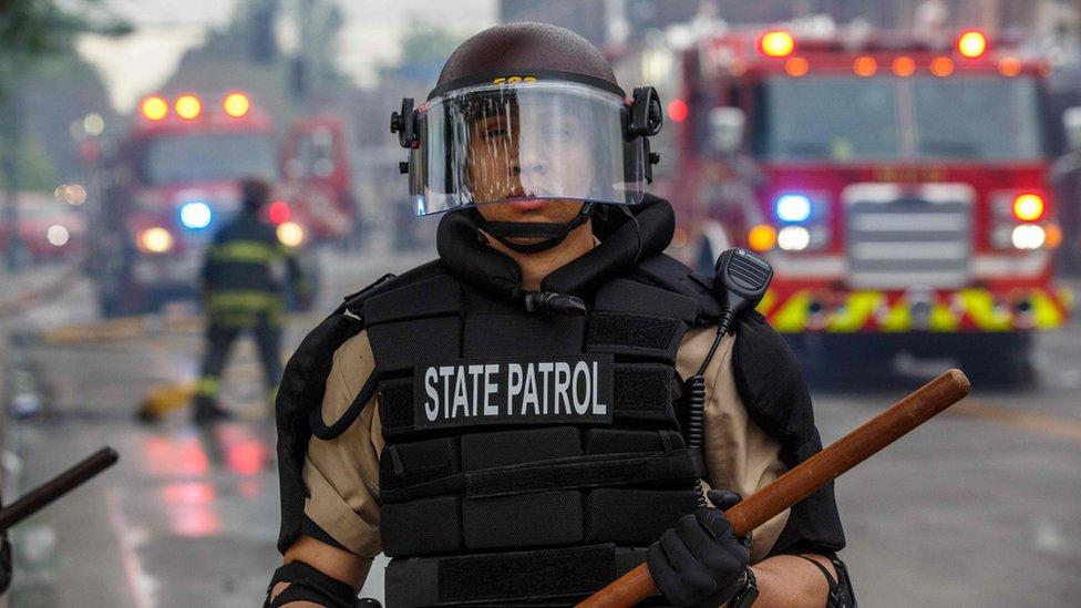 Un miembro de la patrulla estatal de Minnesota con camiones de bomberos detrás