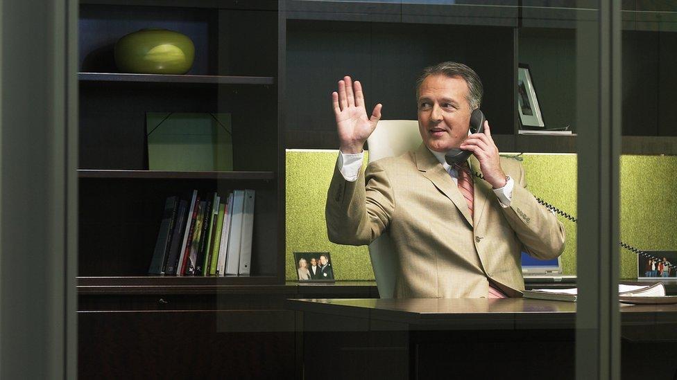 Ejecutivo saludando desde su oficina