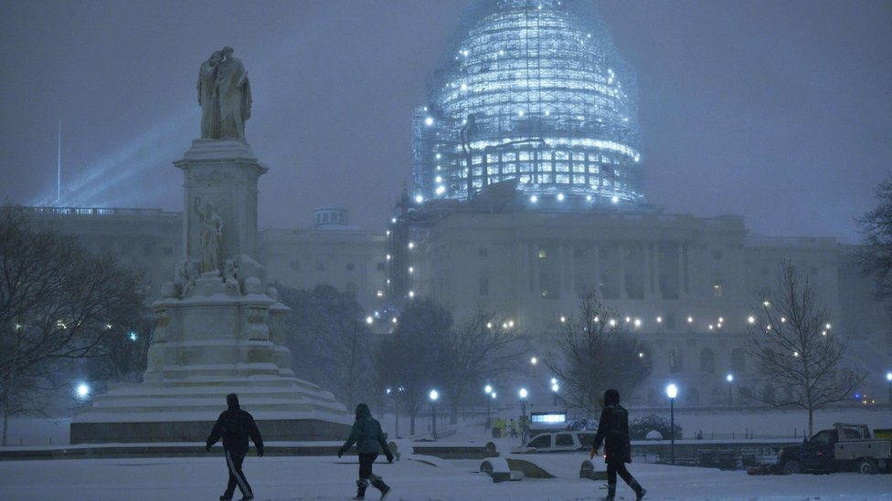 Pedestrians outside the US Capitol in the snow, Washington DC (23 January)
