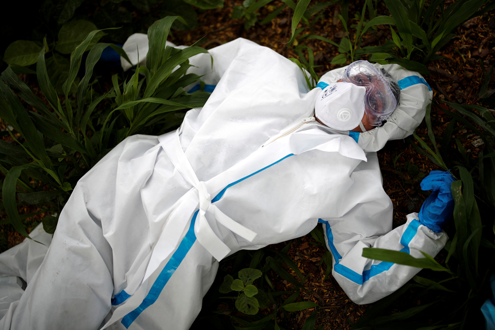 A health worker wearing protective clothing rests on the ground in India