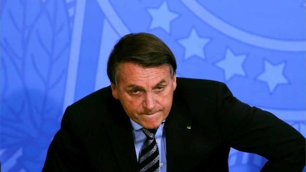 Bolsonaro sentando, com cara um pouco tensa, em evento, diante de painel azul