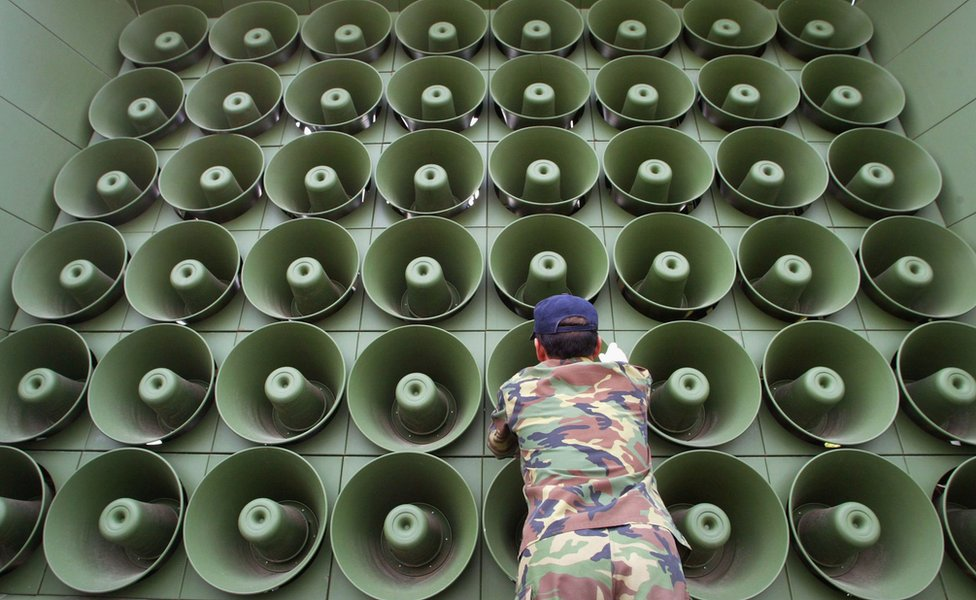 Man standing in front of a speaker stack