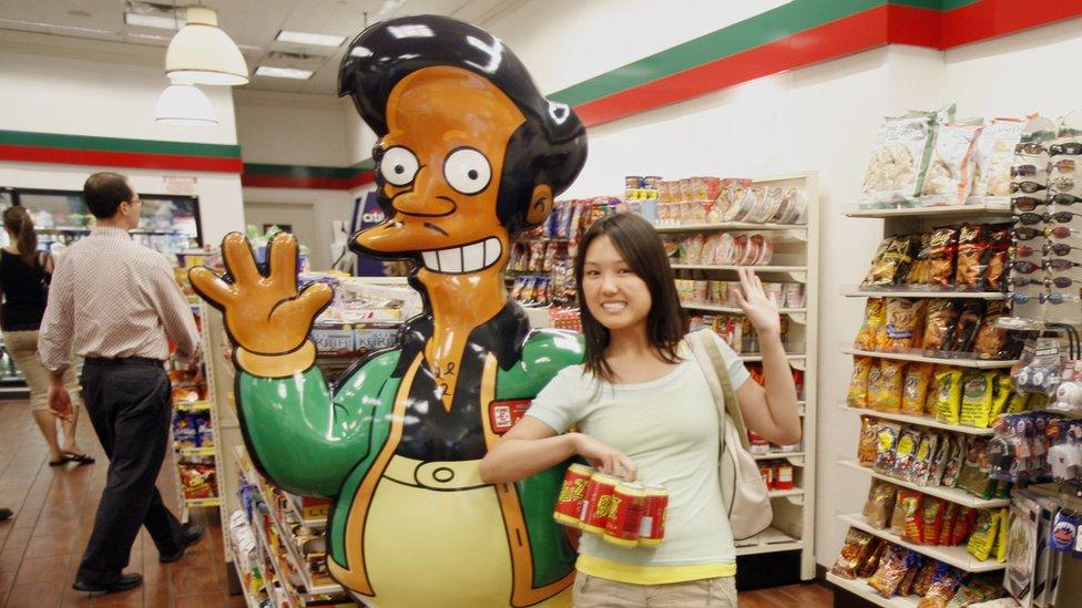 Una mujer posa con un muñeo de Apu.