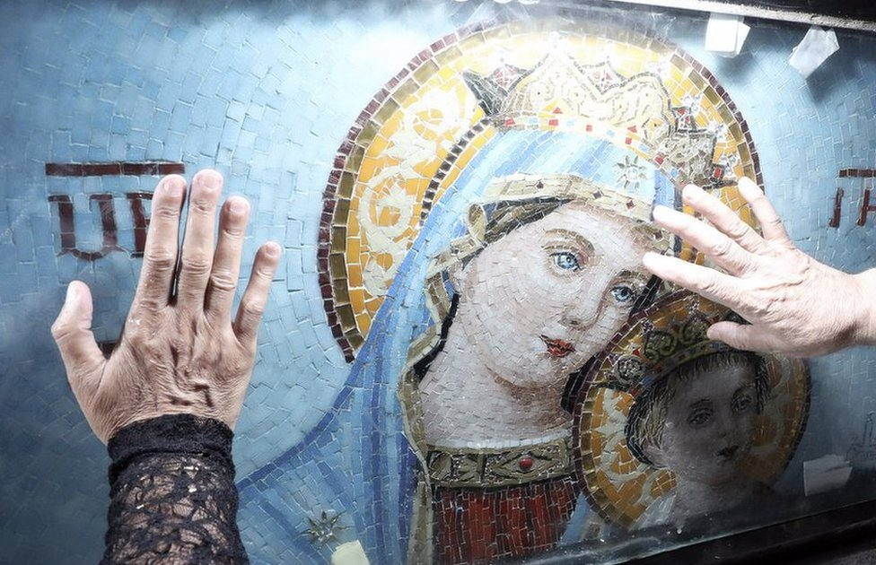 People touch a depiction of the Virgin Mary after a mass at Cairo's Historical Church of Blessed Virgin Mary.