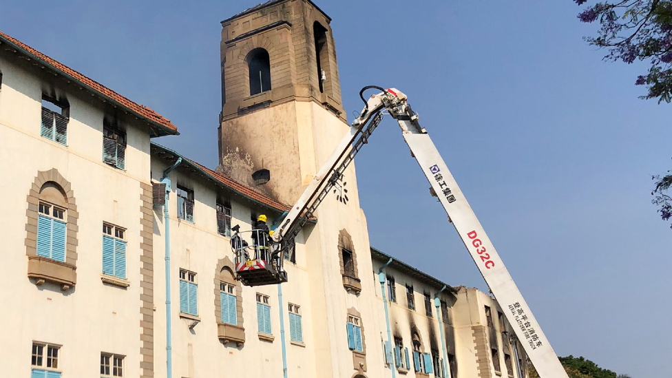 "A photo tweeted by Makerere University showing firemen investigating the ""Ivory Tower"" the morning after the blaze, Kampala, Uganda - 20 September 2020"