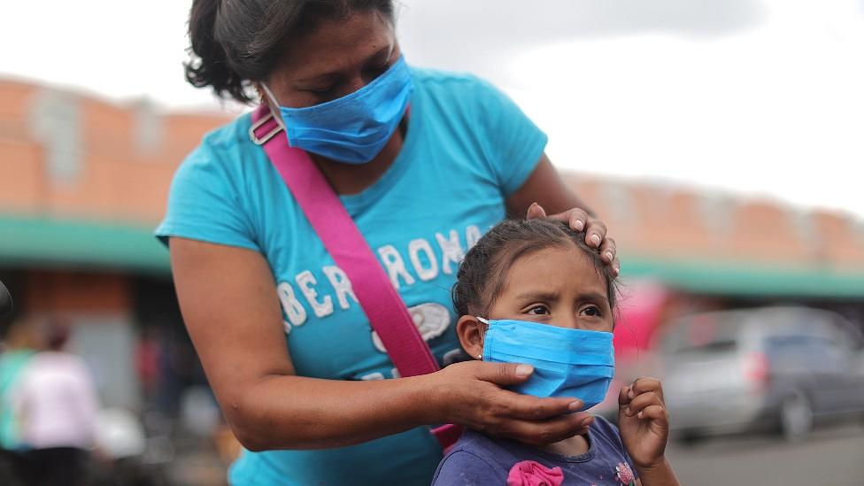 Madre con su hija en México. Ambas llevan tapabocas.