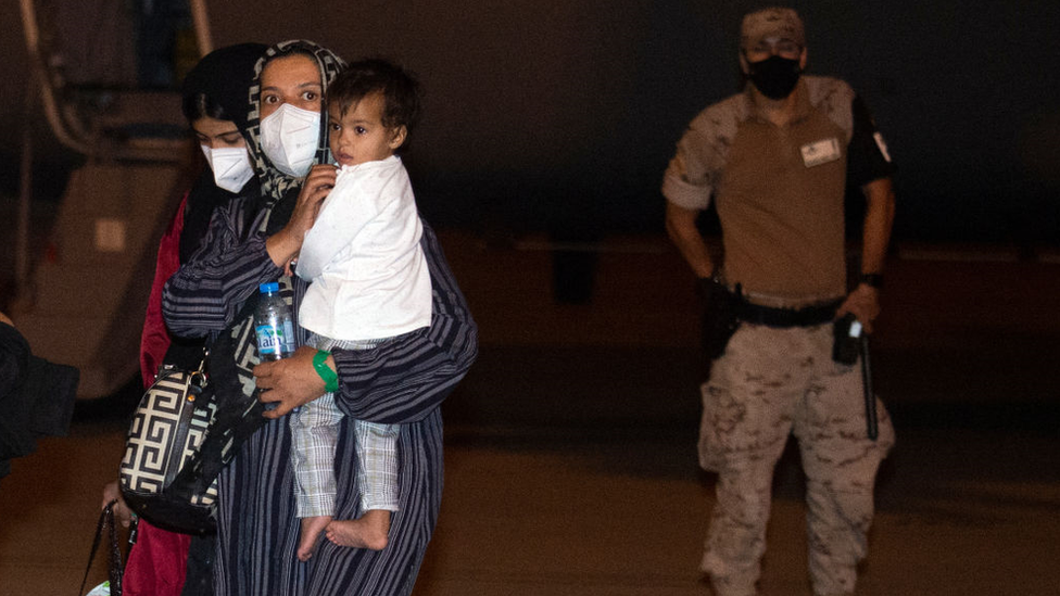 Two Afghan women with a child walk past a Spanish soldier after disembarking from an airplane