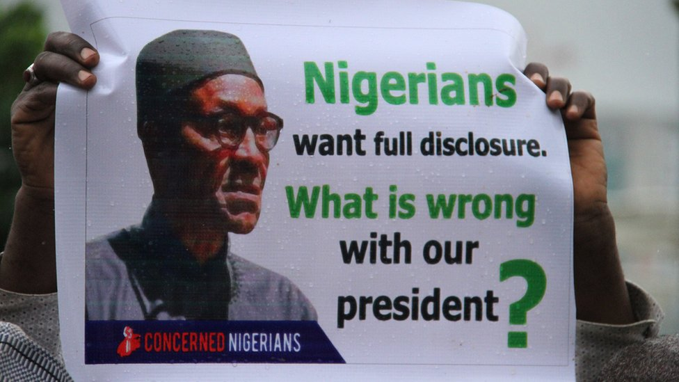 """Poster reading: """"Nigerians want full disclosure. What is wrong with our president?"""""""