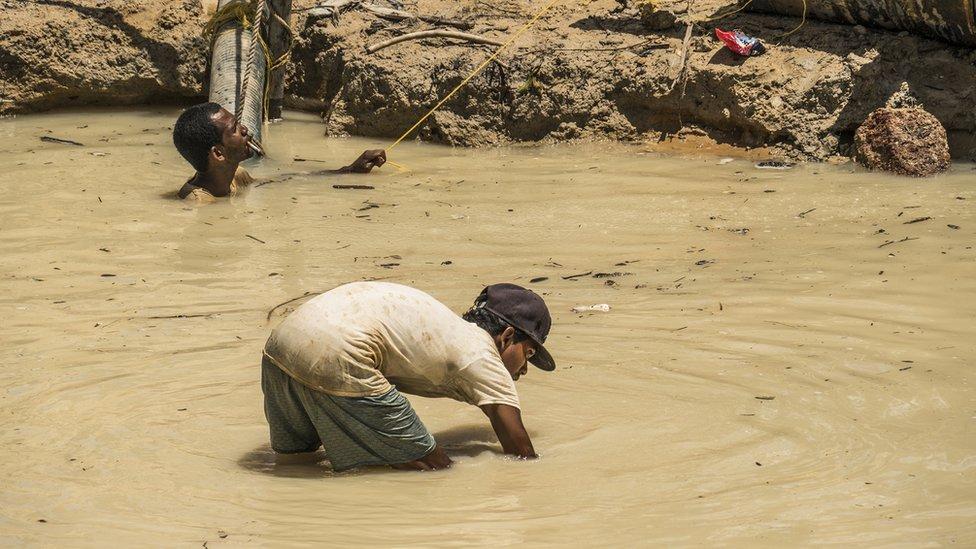 Trabajadores en una mina de oro laboran en agua sucia en la región Mazaruni, Guyana
