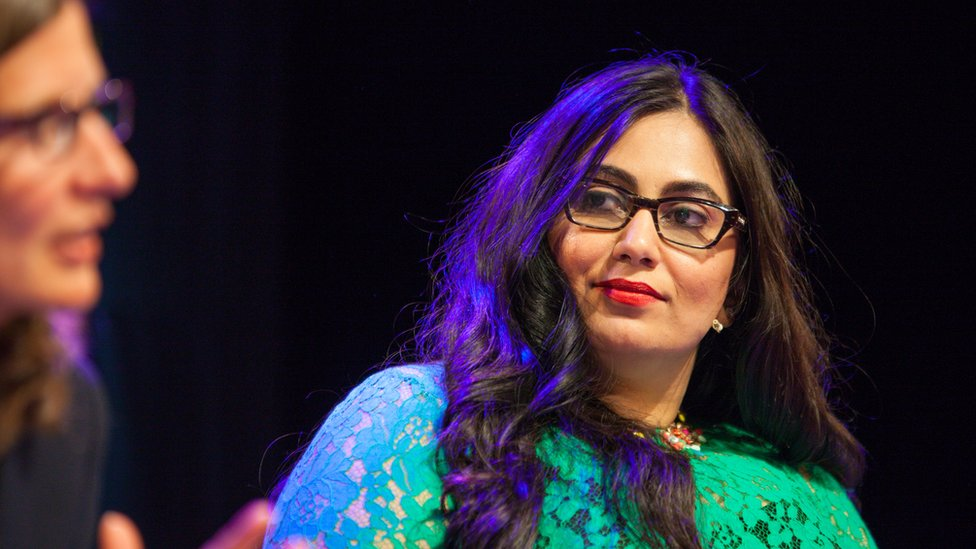 Shazia Awan-Scully, She is wearing glasses and a turquioise dress as she listens to the debate