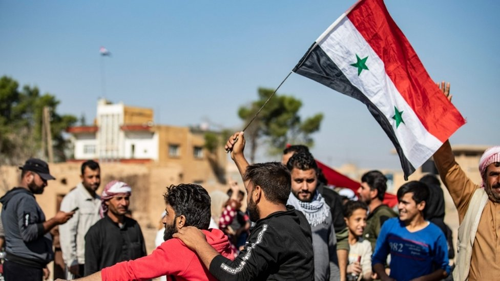 Locals welcome Syrian regime forces as they arrive at the western entrance of the town of Tal Tamer