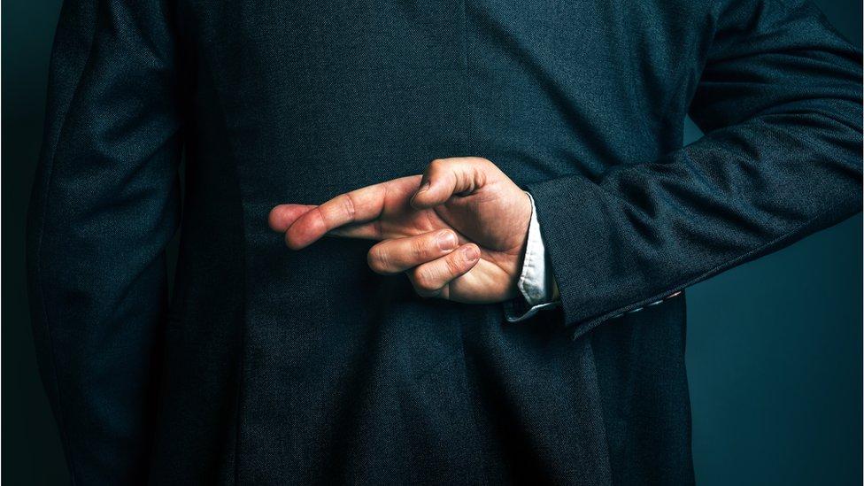 Hombre con los dedos cruzados en la espalda