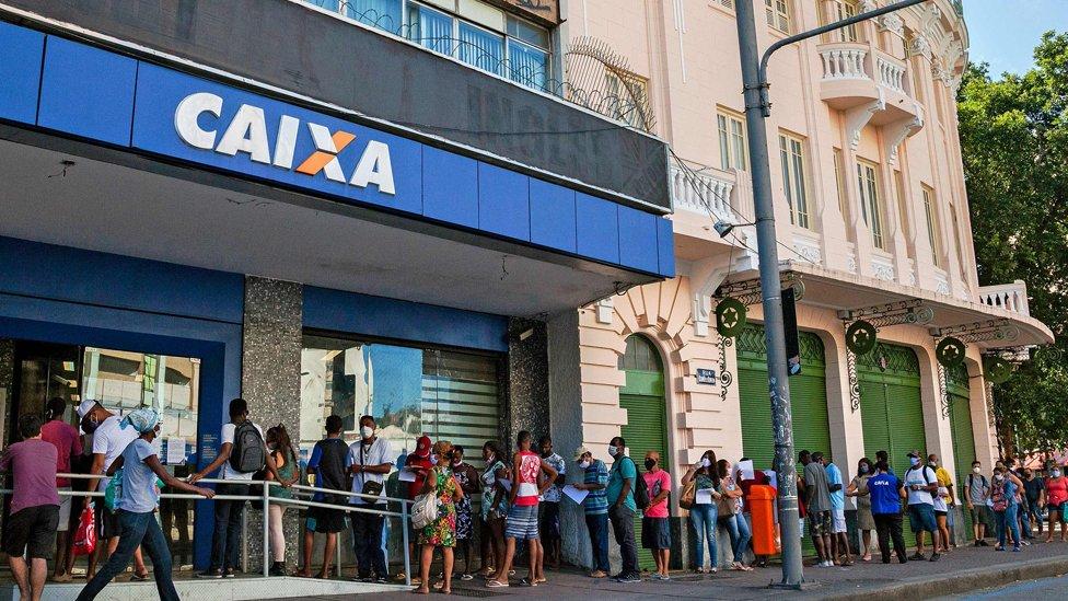 Fila de pessoas em frente à Caixa Econômica Federal esperando para receber o auxílio emergencial