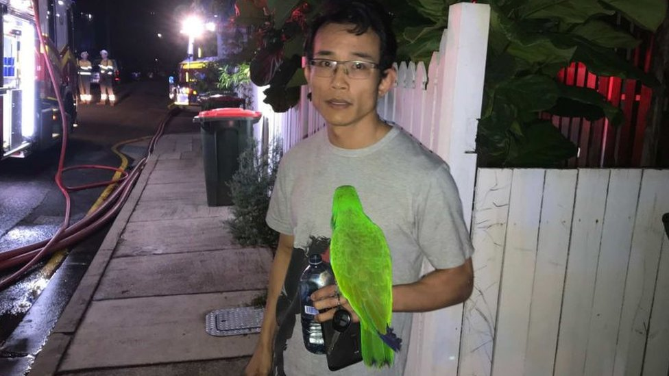 Anton Nguyen with his green parrot, Eric, stands outside his home in front of a fire truck