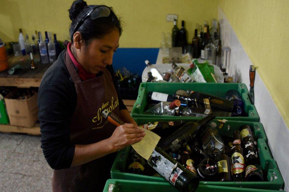 Mujer reciclando vidrio en Guatemala.