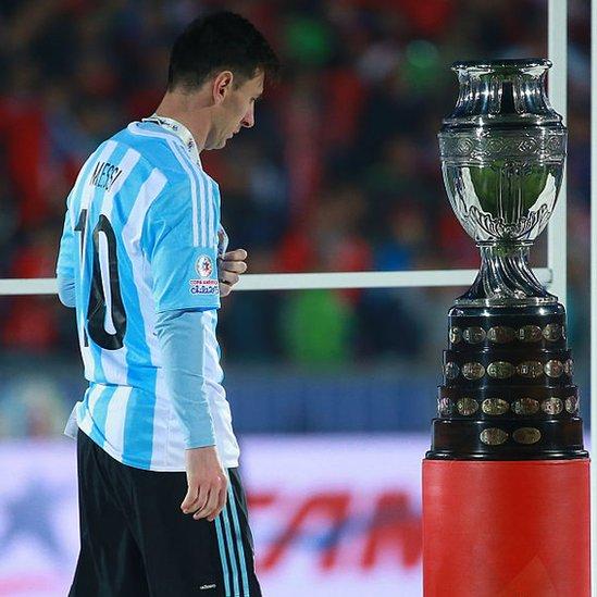 Lionel Mess pasa por al lado del trofeo de la Copa América.