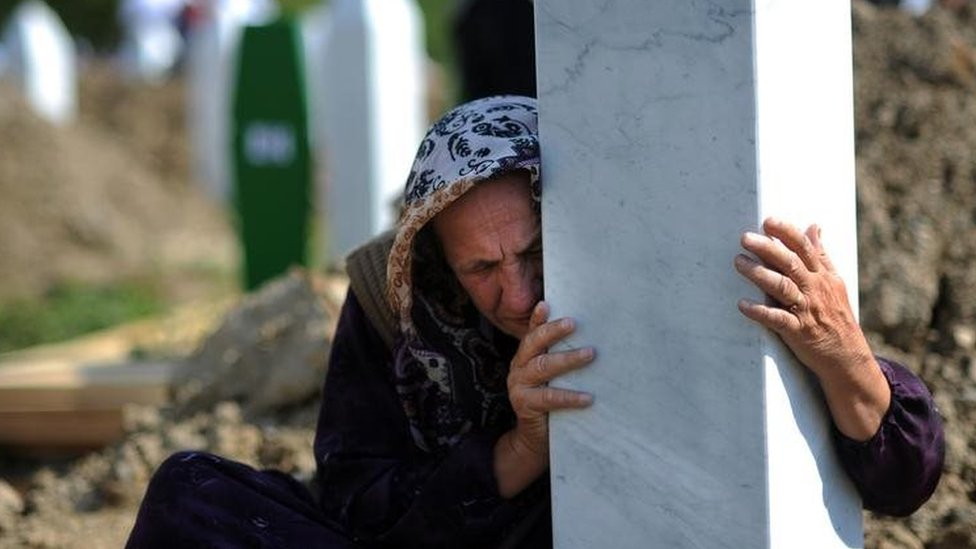 A Bosnian woman embraces a grave stone during a mass burial of newly identified victims of the 1995 Srebrenica massacre at the Potocari memorial cemetery. Photo: July 2010