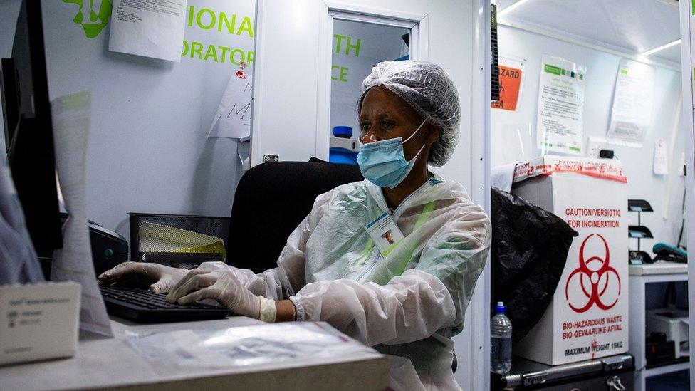 Um membro da equipe médica do Departamento de Saúde da África do Sul trabalha em um computador em uma unidade móvel de teste no Aeroporto Internacional O.R Tambo em Ekurhuleni em 30 de dezembro de 2020, onde os passageiros que apresentam sintomas de COVID-19 na chegada são testados