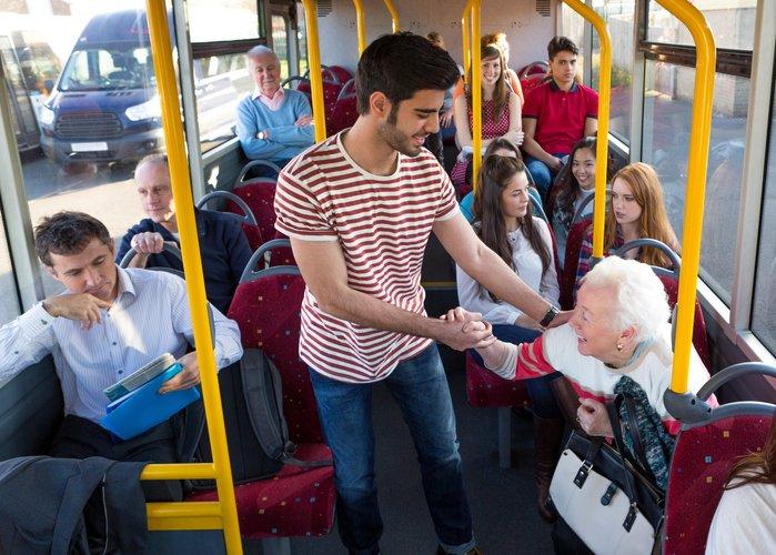 Un joven ayuda a una anciana