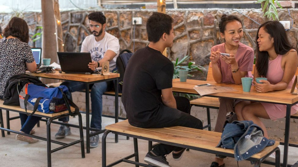 mladi piju kafu u kafeu u Indiji