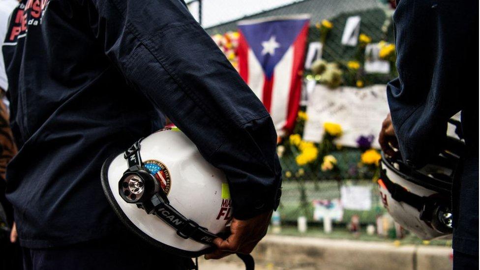 Rescatistas frente al sitio creado espontáneamente en honor a las víctimas de la tragedia en Surfside