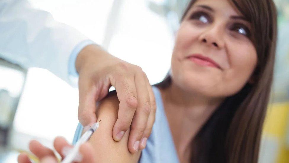 Mulher sorridente recebendo uma vacina no braço