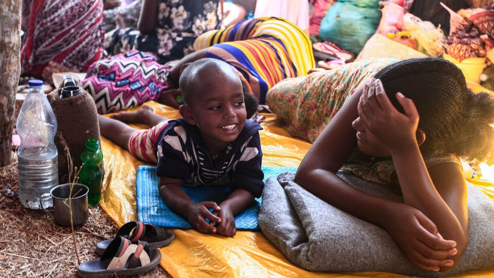 Children and family members lay on mats in their temporary home on 16 November.