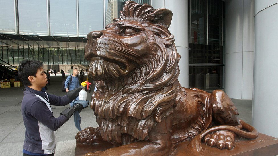 A worker cleans one of the lion statues displayed at the entrance of HSBC bank headquarters in Hong Kong, 05 March 2007
