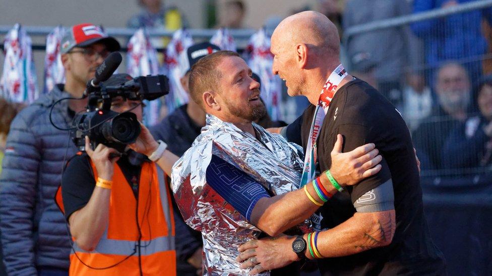 Shane Williams greets Gareth Thomas at the end of the Ironman triathlon