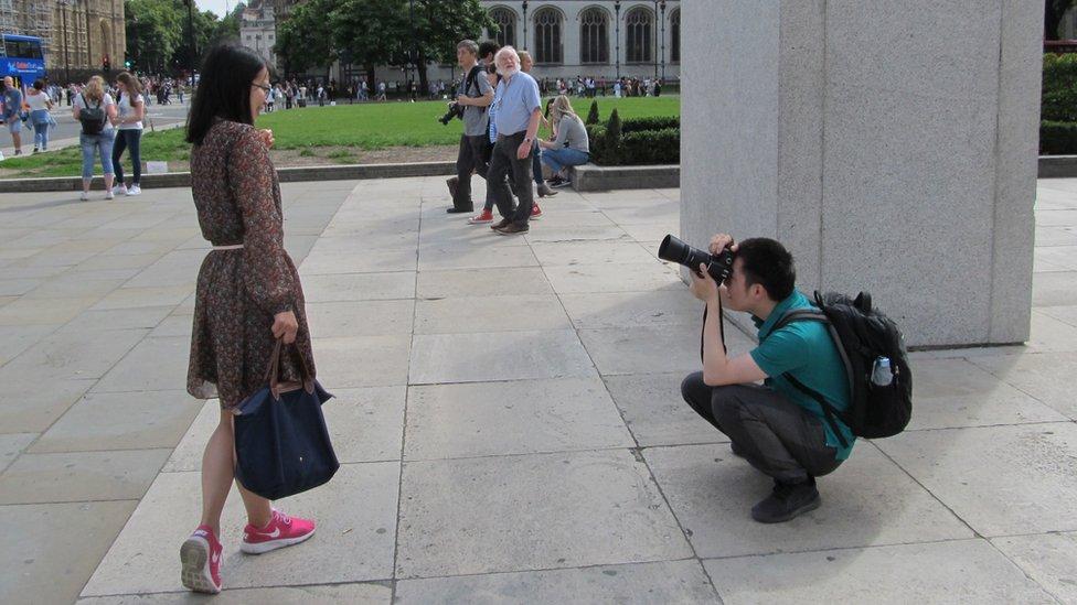 A man kneeling down to take a woman's photograph