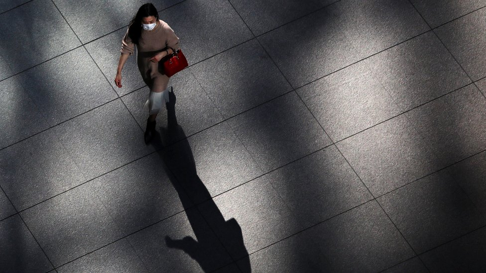 A woman wearing a face mask walking in an empty area in Tokyo