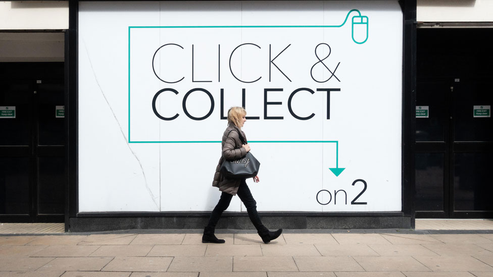 A female pedestrian walks in front of a click-and-collect point on the High Street.