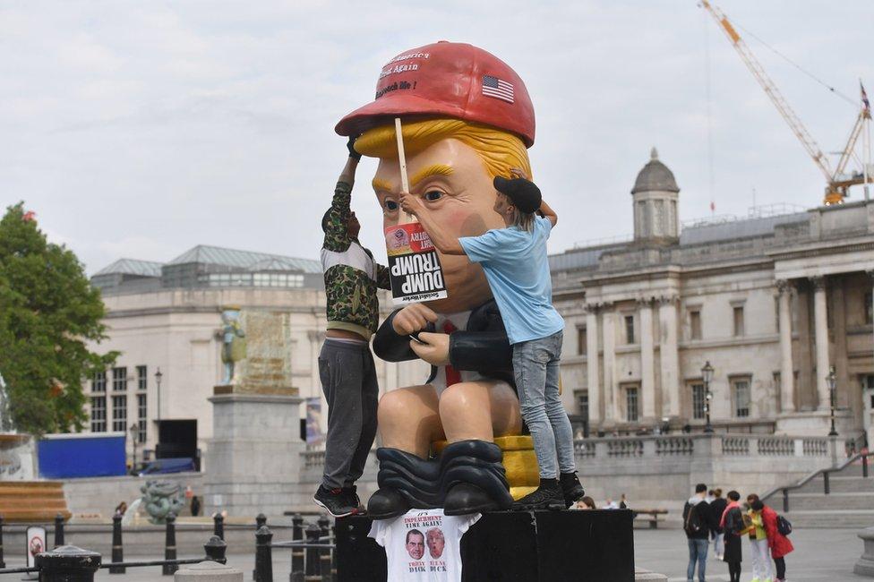 Pet metara visoke statue Trampa kako sedi na zlatnoj klozetskoj šolji