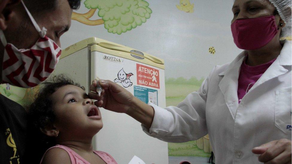 Agente de saúde vacina criança em Manaus