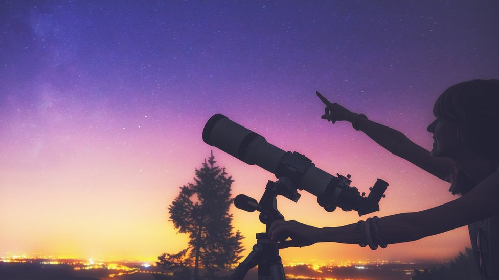 A person points at the sky while holding a telescope.