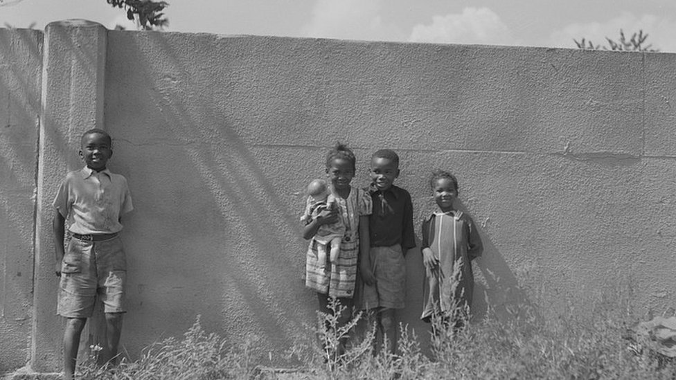 Niños negros apoyados en el muro