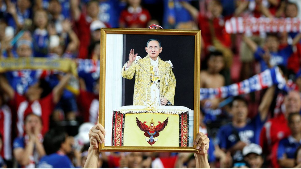 "A soccer player from the Thai national team displays a picture of Thailand""s King Bhumibol Adulyadej after winning the ""King""s Cup"" at Rajamangala stadium in Bangkok, Thailand, June 5, 2016."