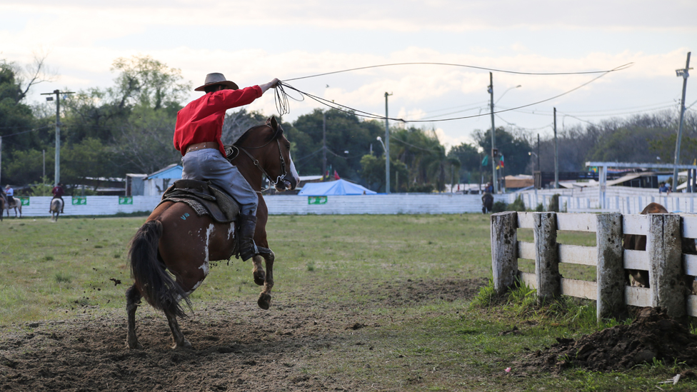 A man rides his horse, lasso in hand, during the rodeo