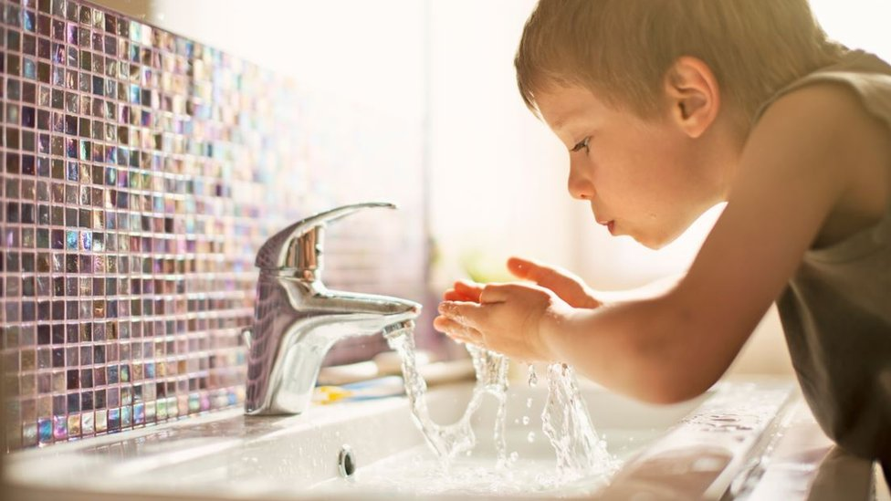 A little boy splashing his face with water from a mixer tap