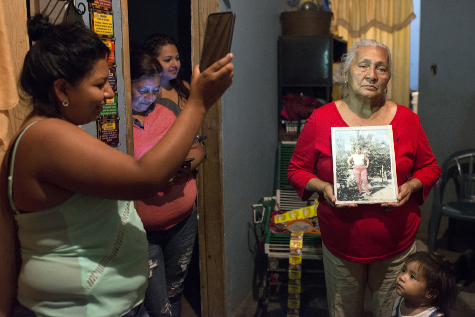 Edita Maldonado holds a picture of her late daughter Rosa while Sirly holds up her phone to provide light and Sandra and Greicy watch