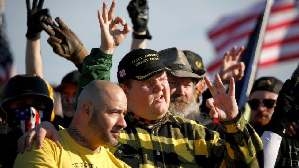 Far-right Proud Boys gather near the Washington Monument, 12 December, making racist gestures