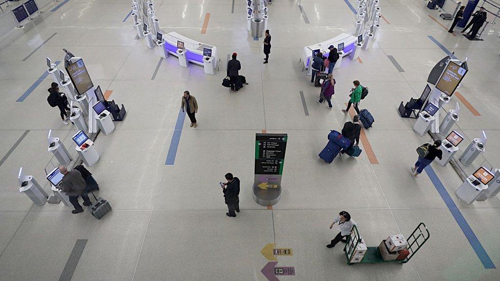Viajeros pasan por el vestíbulo de facturación de la terminal B del Aeropuerto Internacional Logan de Boston el 2 de abril de 2020