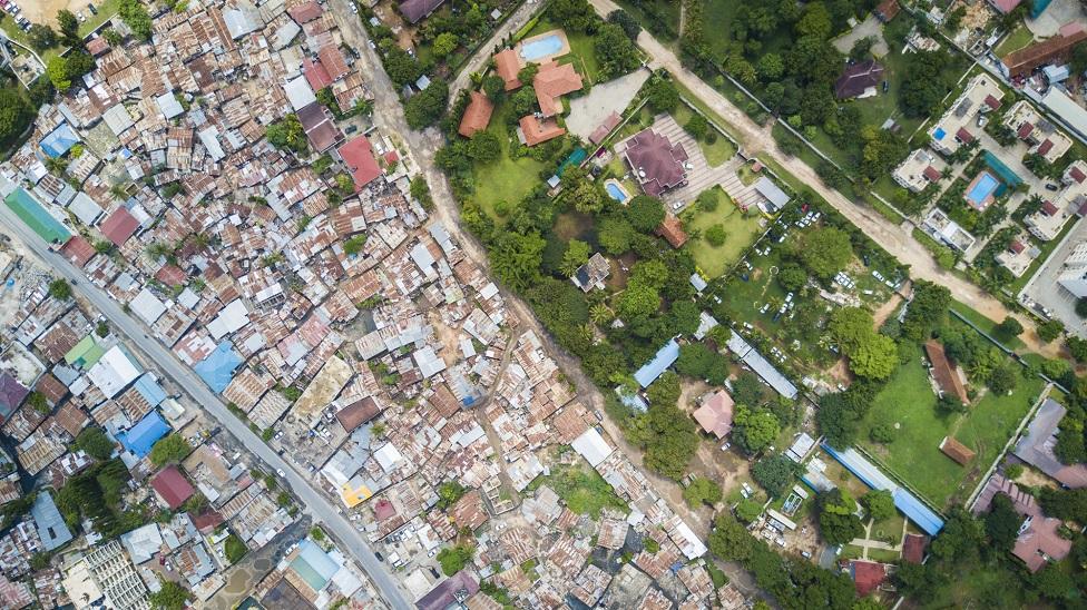 Foto aérea de grandes residencias coloniales en Oyster Bay, Sudáfrica y un asentamiento pobre vecino